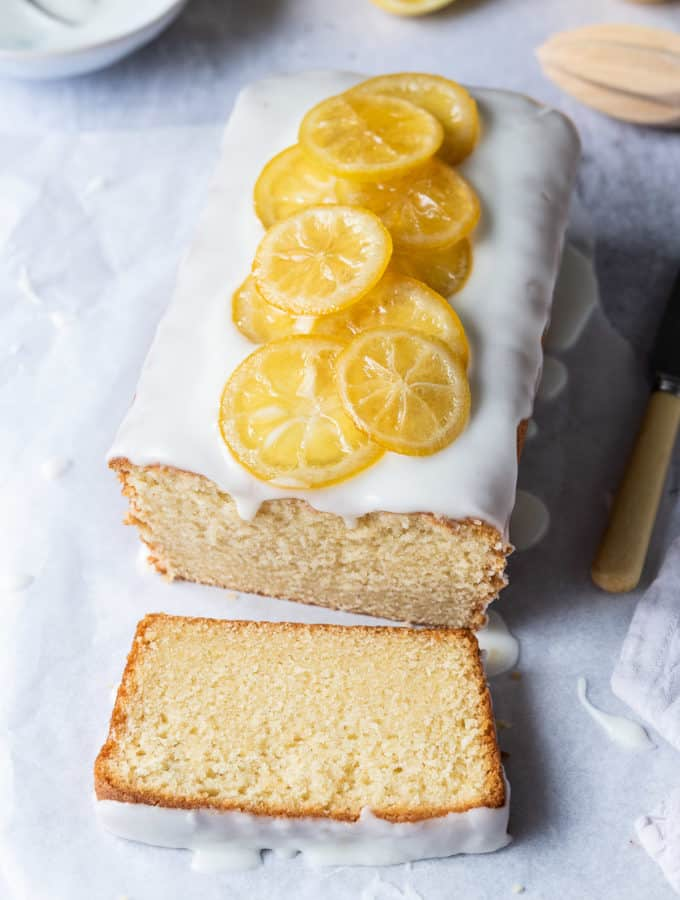 a loaf of vegan lemon pound cake topped with candied lemon slices on a sheet of white baking parchment with lemons and a bowl of icing.