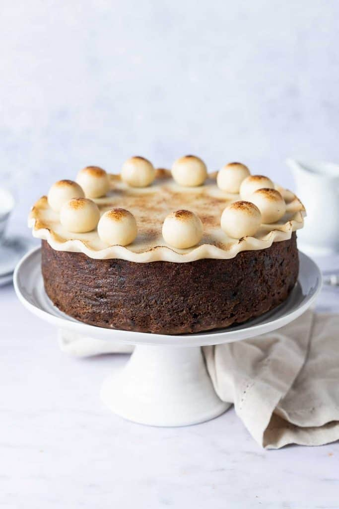 vegan simnel cake on a white cake stand on a light grey background with a cream cloth, white milk jug and teacups.
