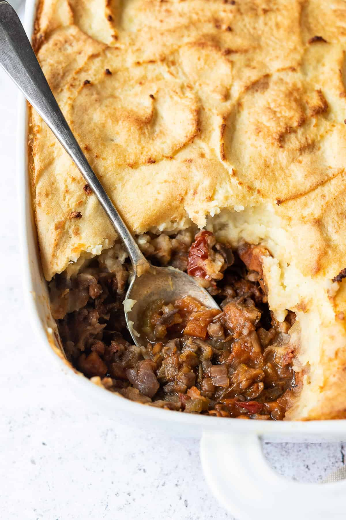 Close up of cottage pie with a spoonful removed.