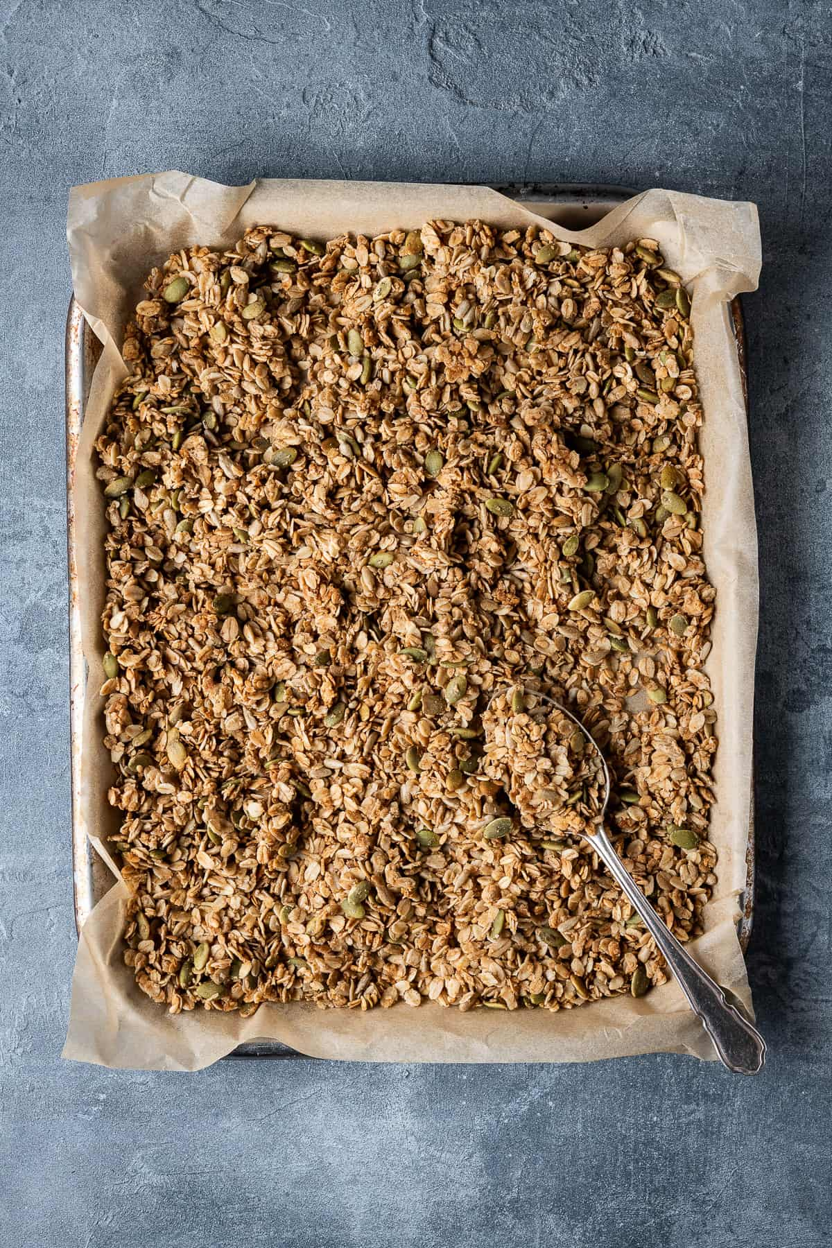 A baking parchment lined tray of granola on a grey background.