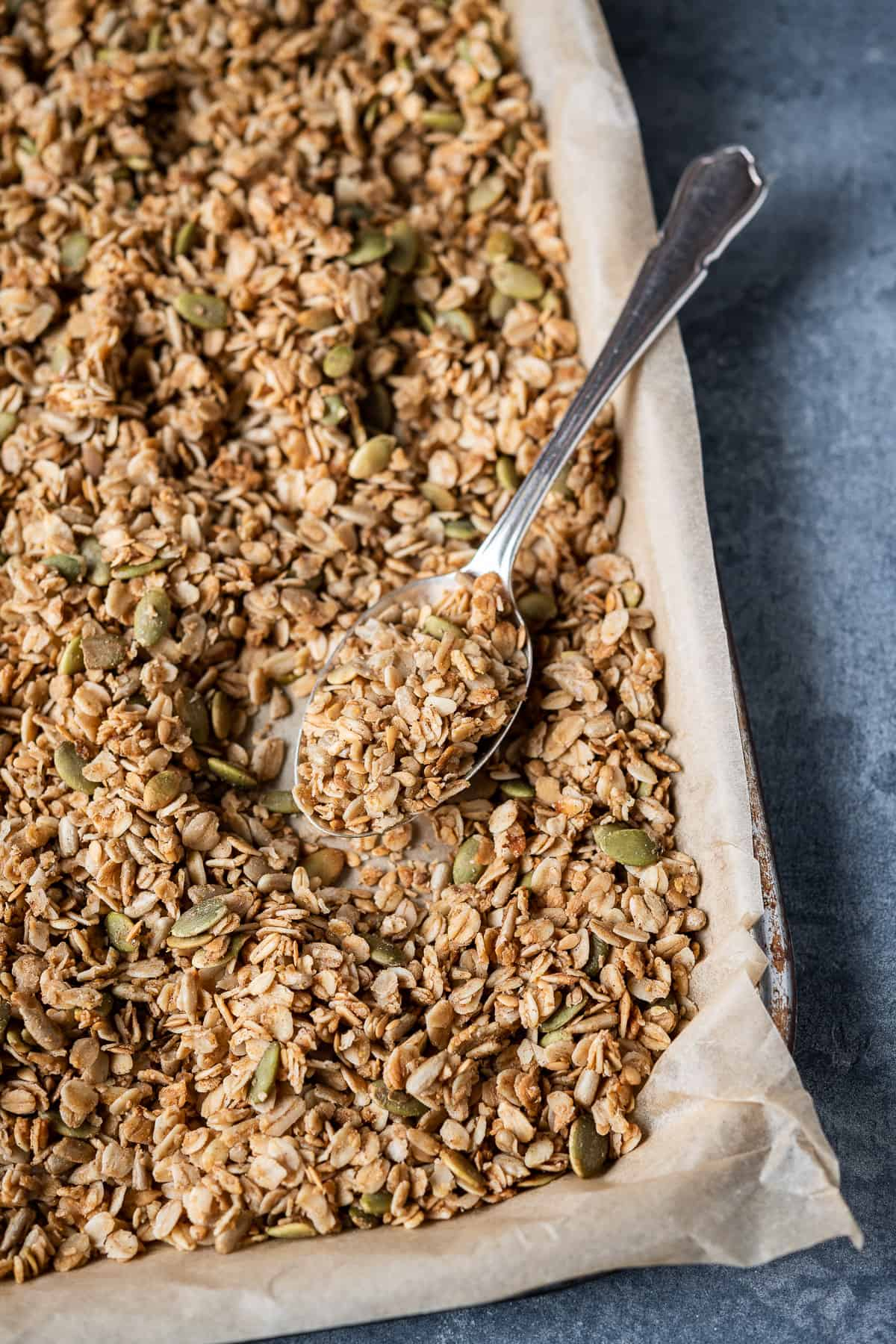 Vegan granola on a baking tray with a metal spoon.