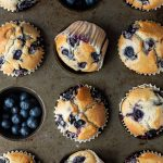 Close up of vegan blueberry muffins in a metal muffin tray, two of the holes filled with fresh blueberries.