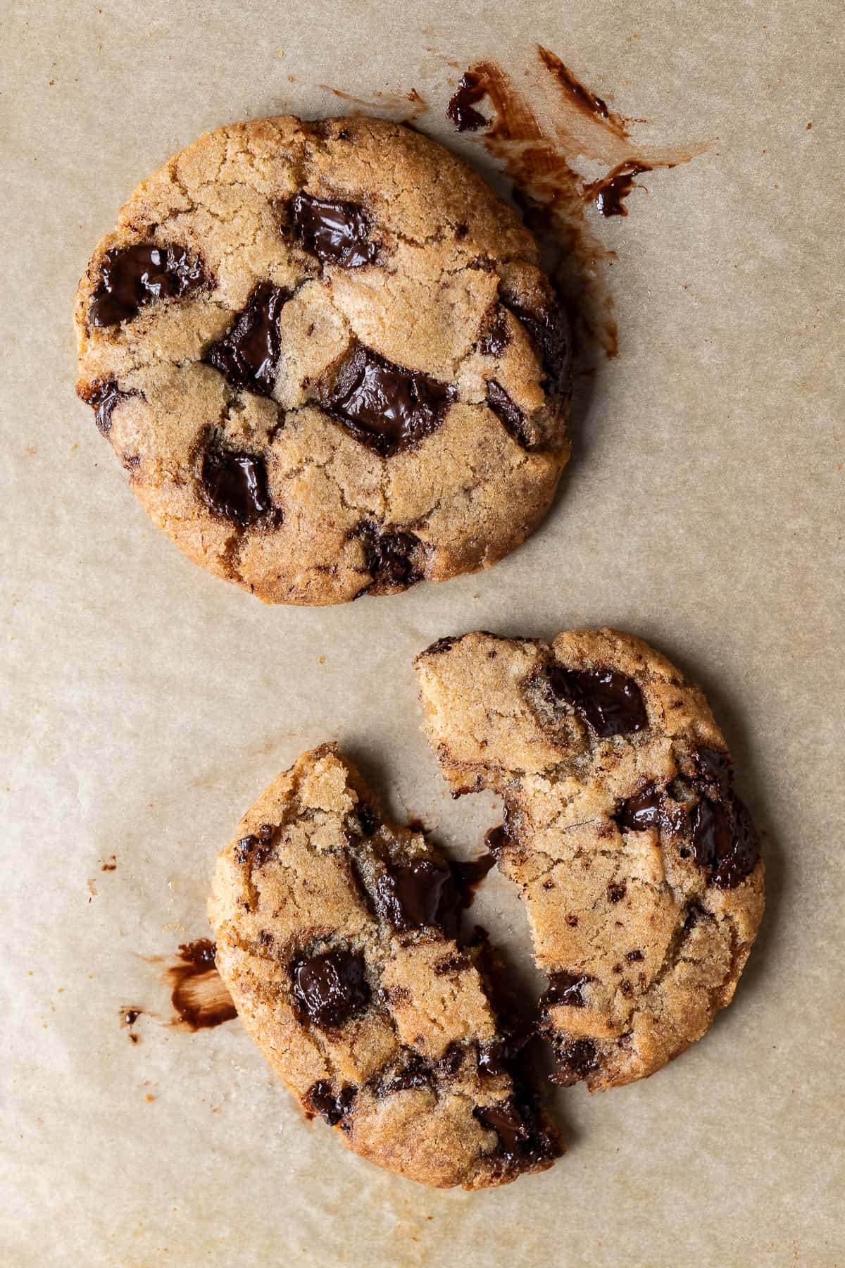 Two vegan chocolate chip cookies for one on a sheet of brown baking parchment