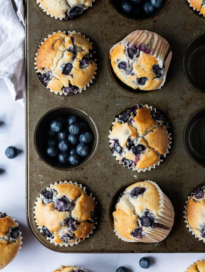 vegan blueberry muffins in a metal muffin tray with fresh blueberries on a marble background.