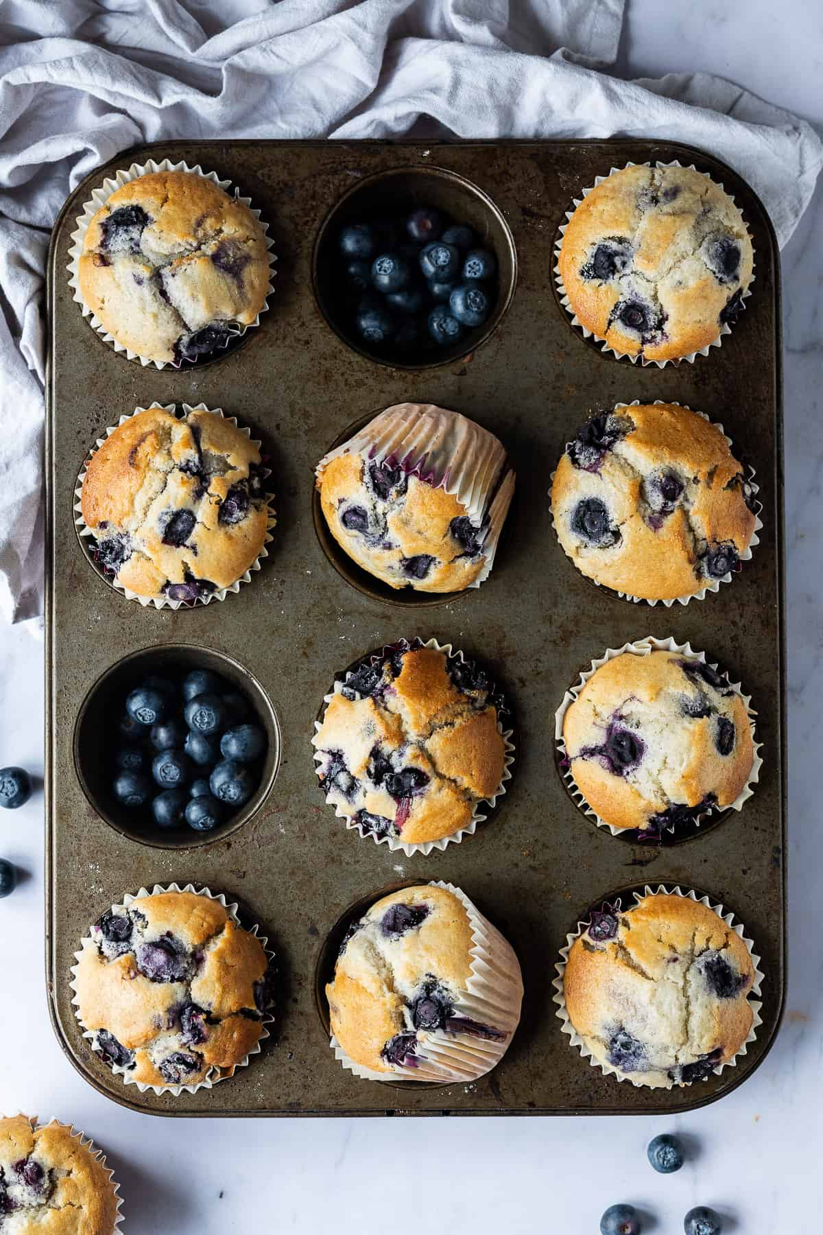 A tray of vegan blueberry muffins on a marble background with a grey cloth.