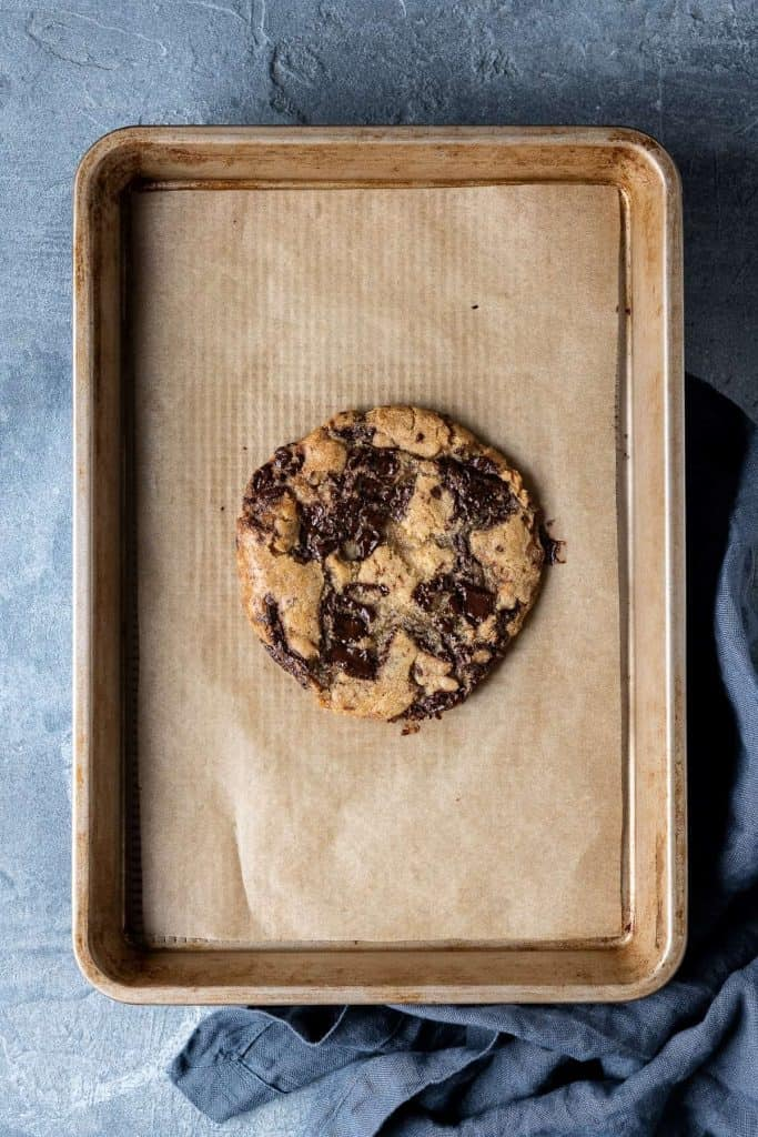 One giant cookie on a baking sheet on a grey background.