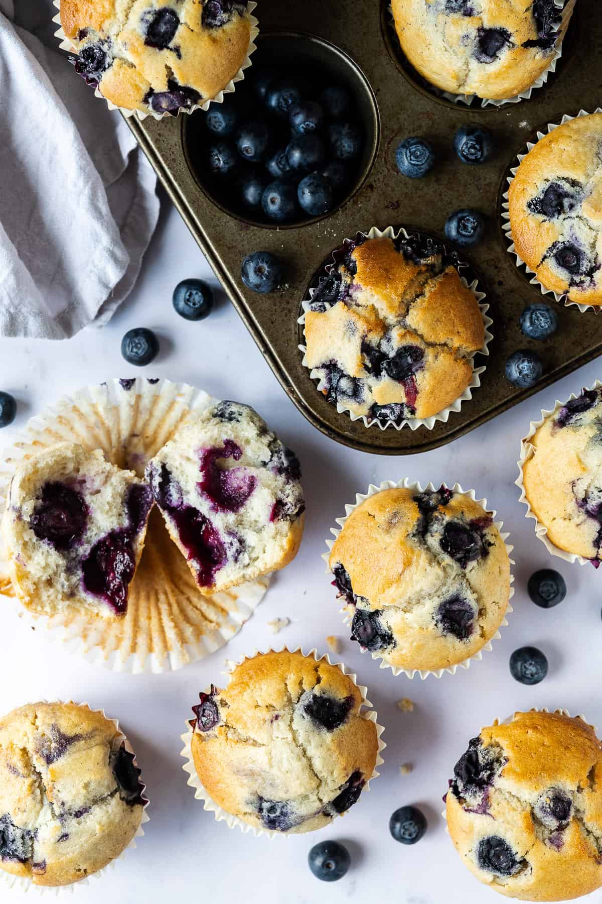 vegan blueberry muffins on a marble surface with fresh blueberries and a muffin tin, one muffin torn in half.