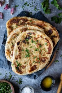 four vegan naan breads on a grey cloth on a dark grey background with garlic, coriander, salt and garlic butter.