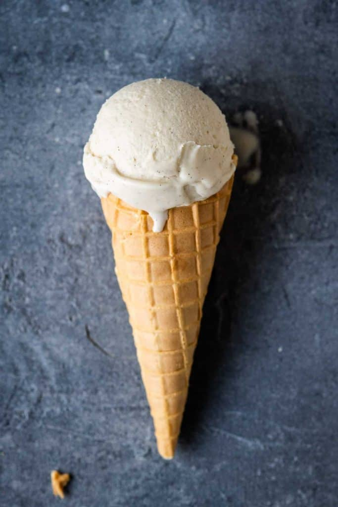 A waffle cone with a single scoop of vegan vanilla ice cream on a grey background.