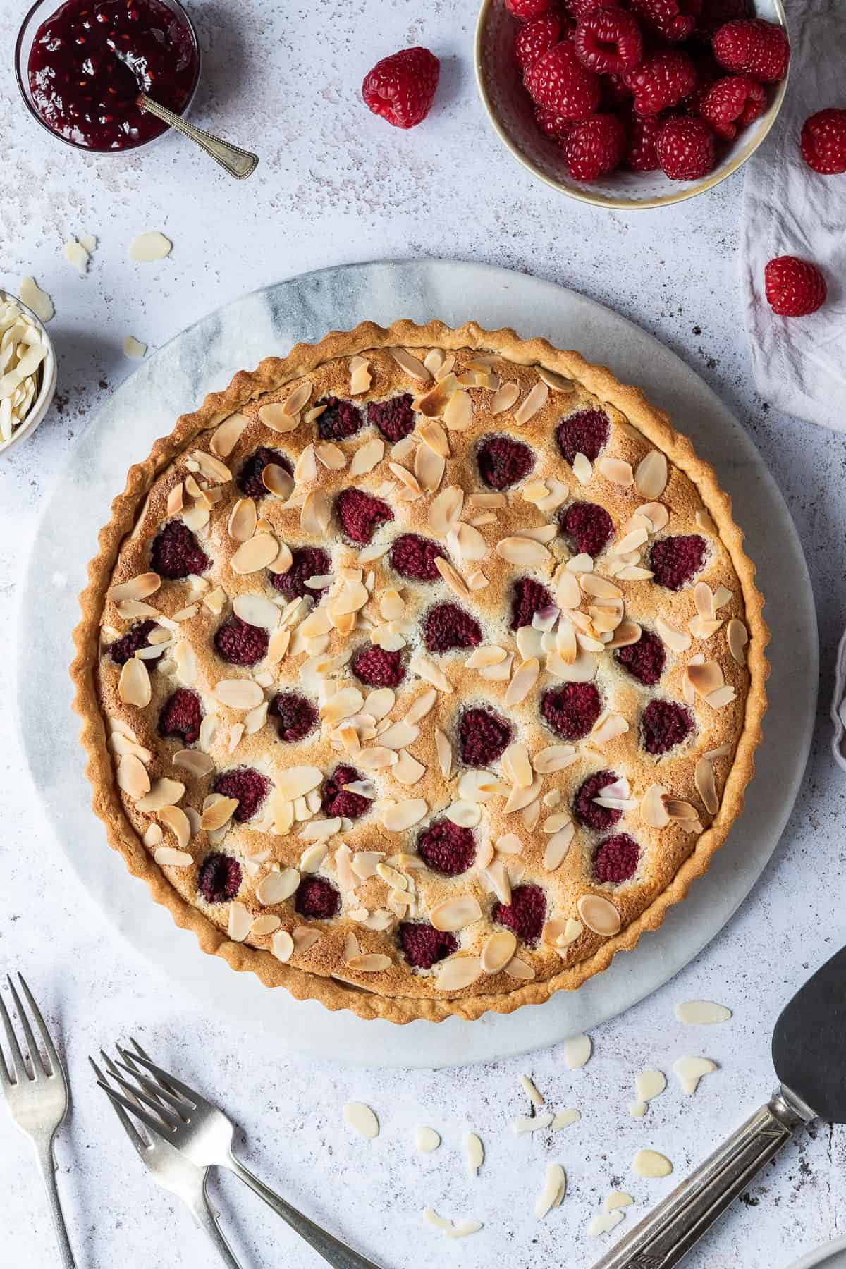 Vegan Bakewell tart on a marble board on a white background.