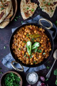 Chana masala in a black metal dish on a dark background with naan bread, fresh coriander, a pot of salt and a spoon.