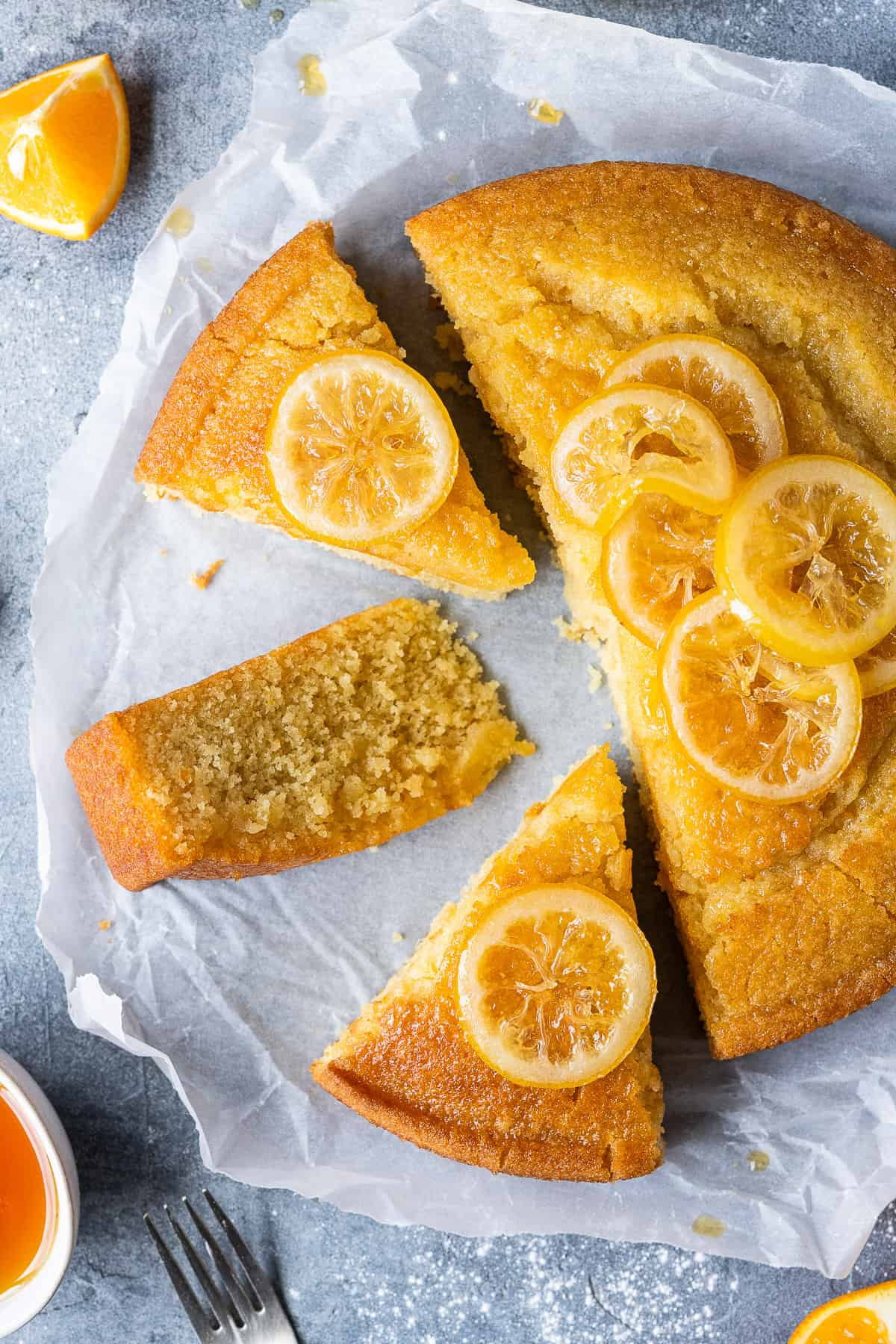 Slices of vegan semolina cake topped with candied lemon slices on a sheet of white baking parchment.