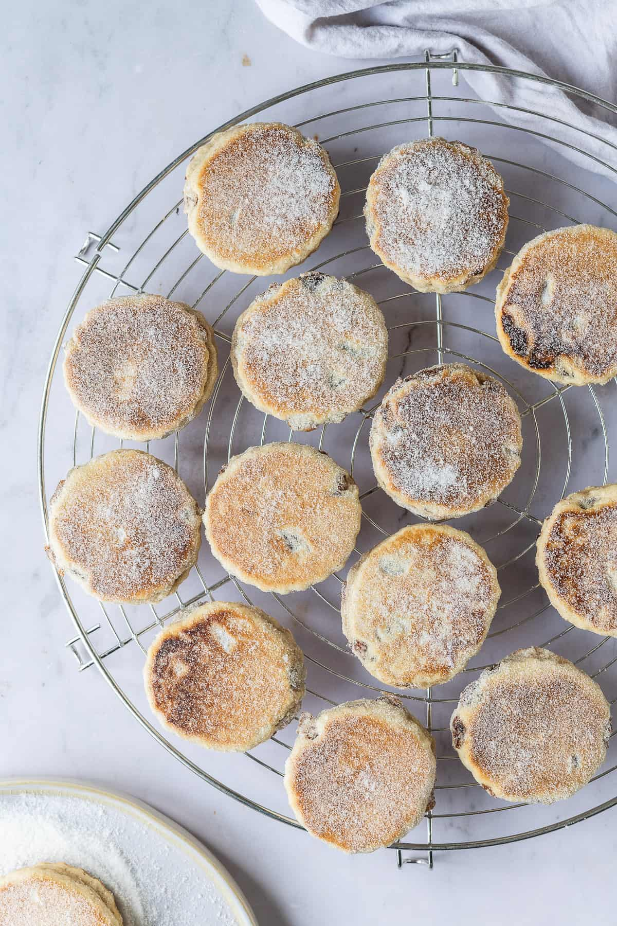 Vegan Welsh cakes on a round wire cooling rack on a marble background.