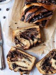Sliced vegan chocolate babka on brown baking parchment on a grey background.