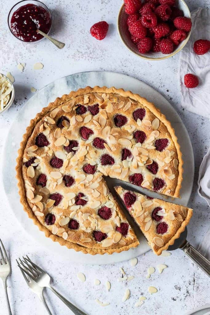 vegan raspberry Bakewell tart on a round marble board on a white background with a bowl of raspberries.