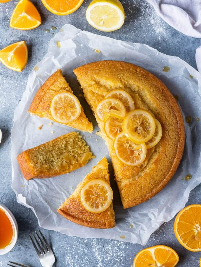 Vegan semolina cake cut into slices on a sheet of baking parchment on a grey background with sliced oranges and lemons