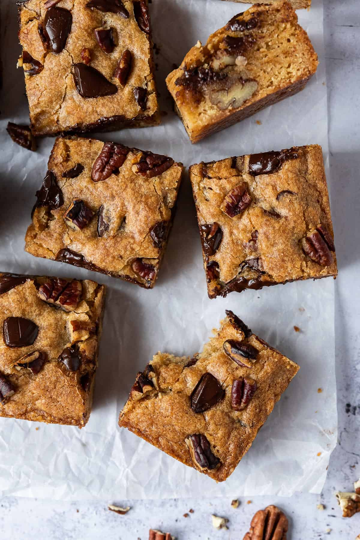 Close up of squares of vegan banana blondies on a sheet of baking parchment