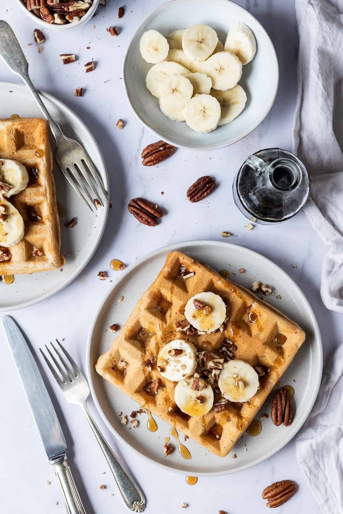 two plates of vegan banana waffles with sliced banana, pecans and maple syrup on a marble background.
