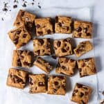 Vegan banana blondies cut into squares on a grey background with chopped pecans and chocolate.