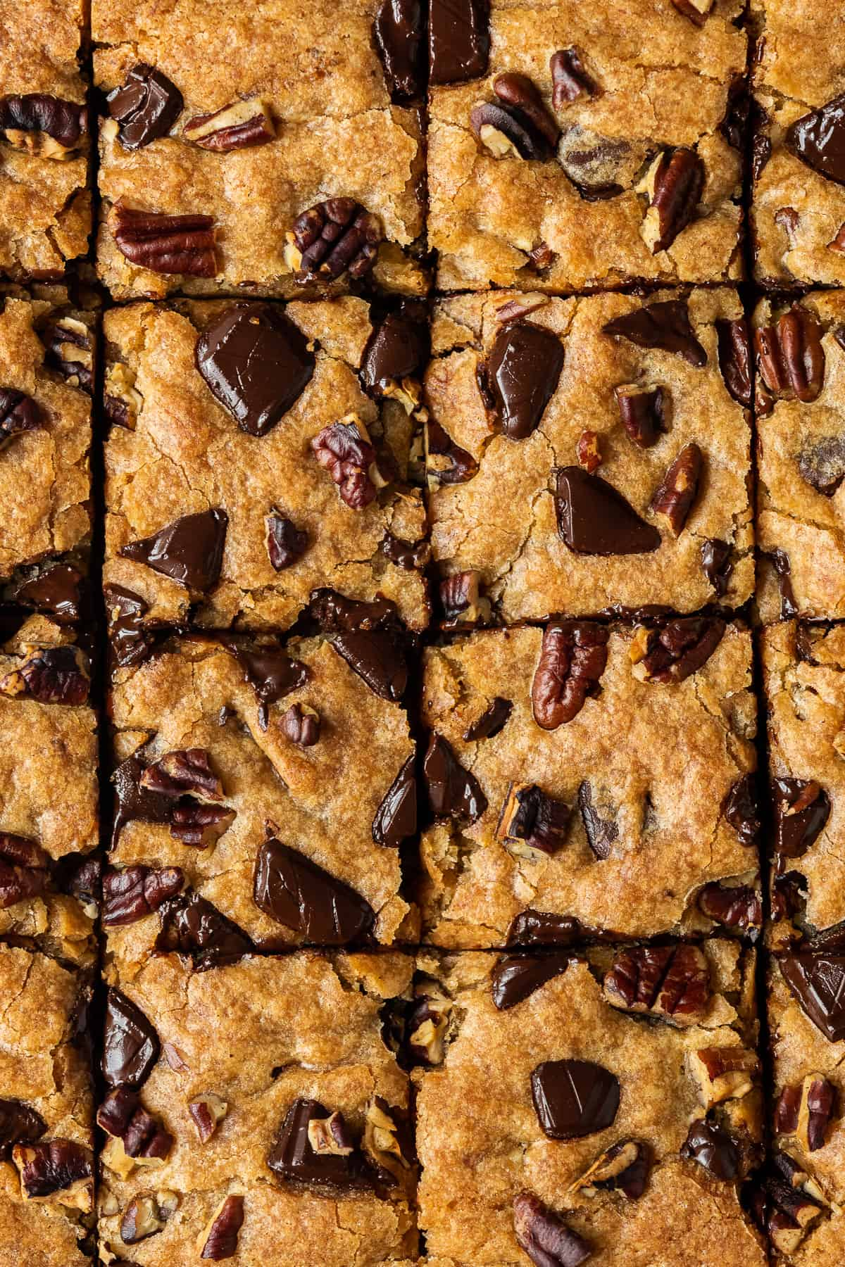 Close up of the top of vegan banana blondies topped with chopped chocolate and pecans.