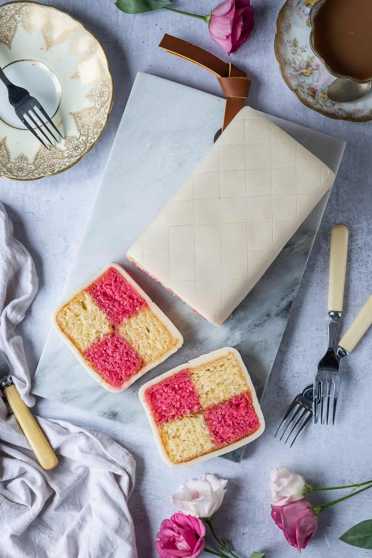 Sliced vegan Battenberg cake on a marble board surrounded by flowers, a grey cloth, pastry forks and a cup of tea.