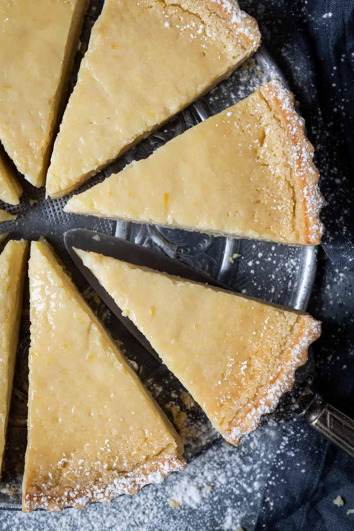 Slices of vegan lemon tart on a metal plate.
