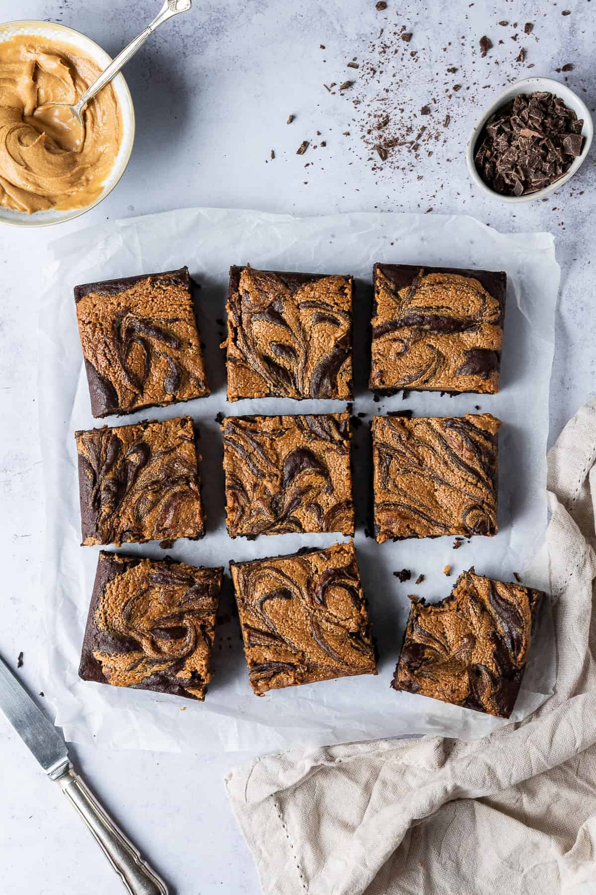 Squares of vegan peanut butter swirl brownie on a sheet of baking parchment with a cloth, a bowl of peanut butter and a bowl of chopped chocolate.