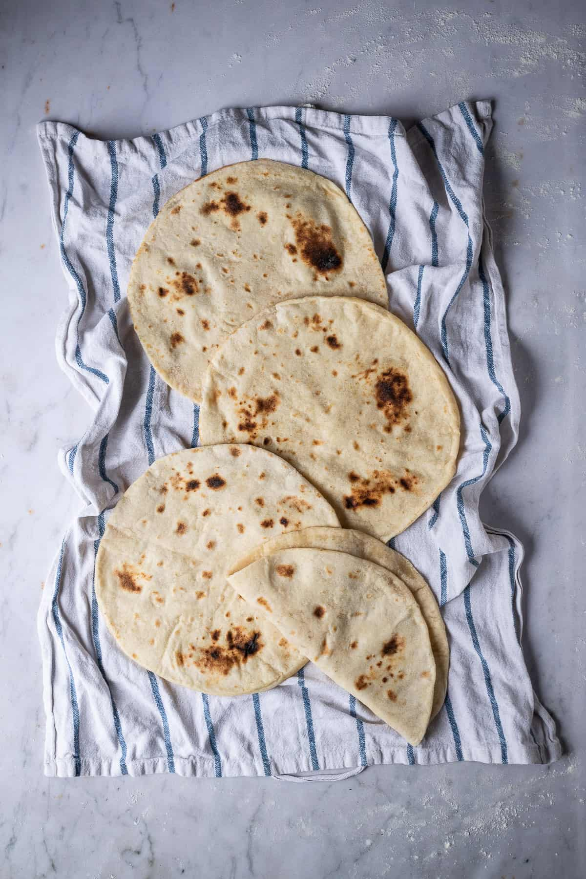 Vegan flatbreads on a tea towel on a marble backdrop