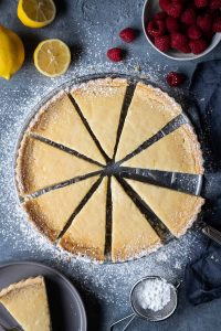 Sliced vegan lemon tart on a grey background with lemons and raspberries.