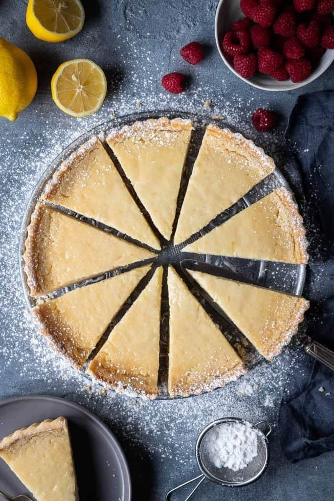 Sliced vegan lemon tart on a grey background with lemons and raspberries.