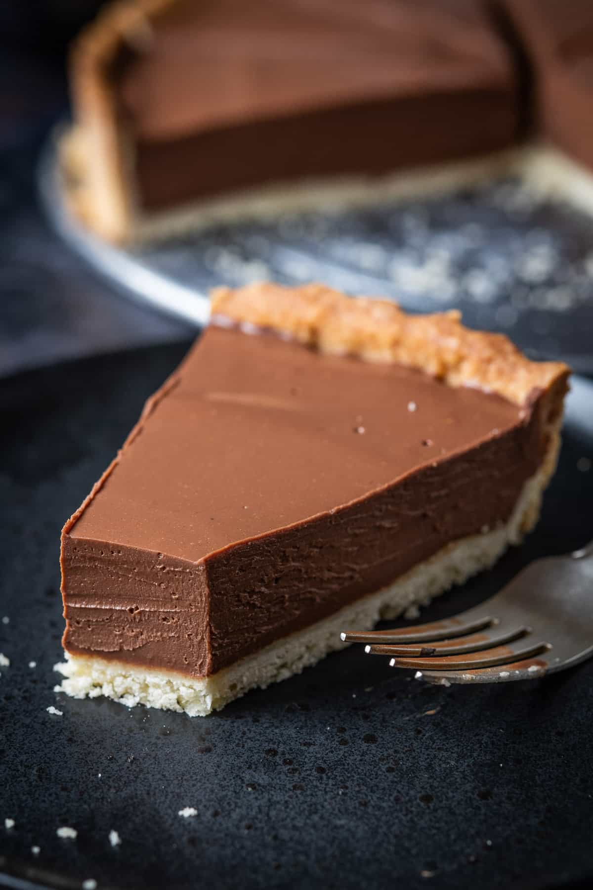 Close up of a slice of vegan peanut butter chocolate tart with a forkful removed.