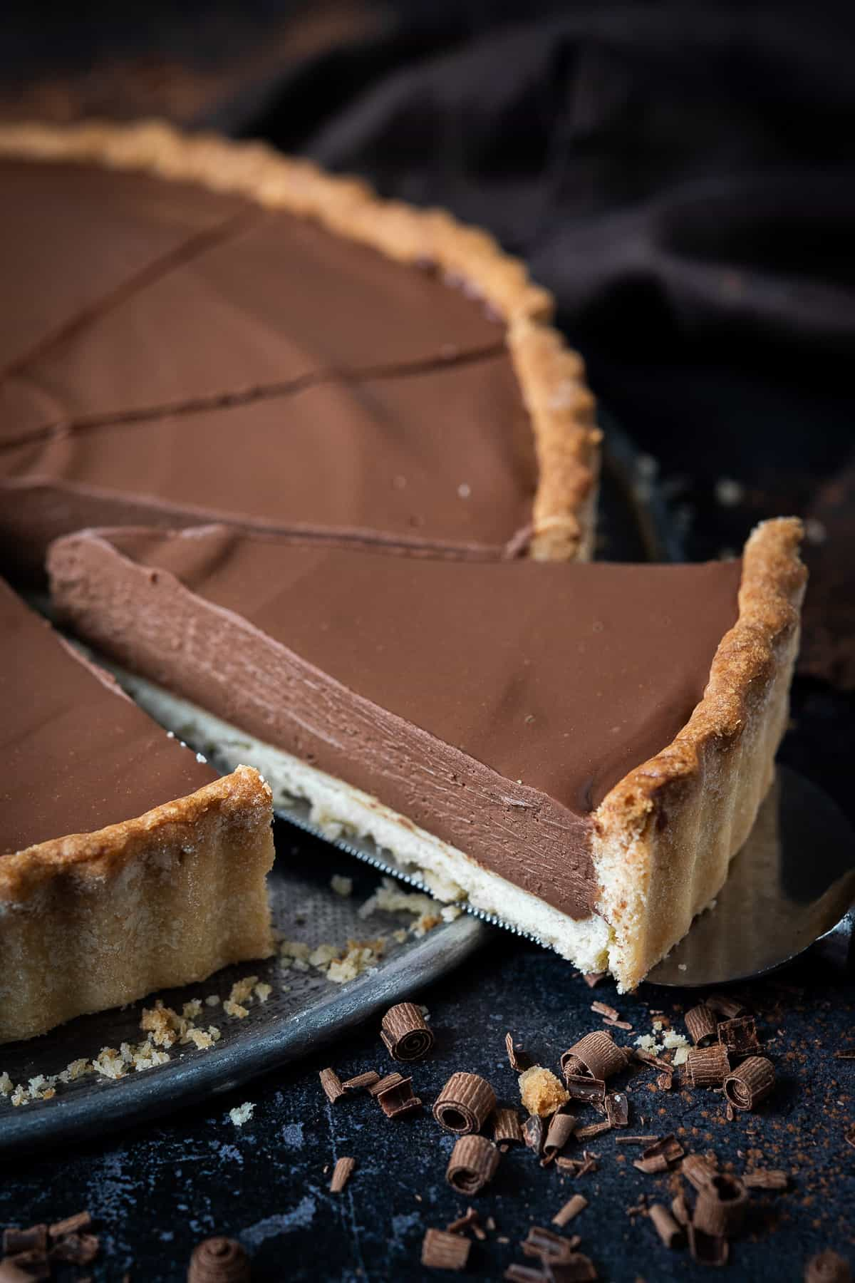 Close up of a slice of vegan peanut butter chocolate tart.
