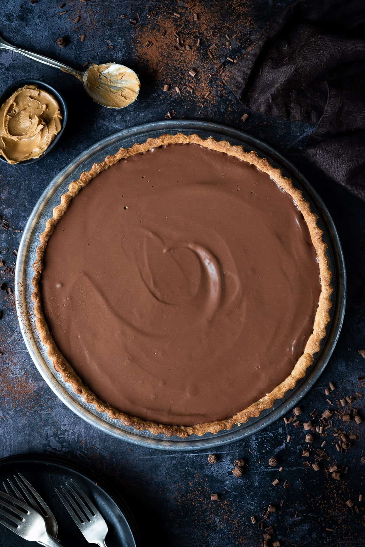 Vegan peanut butter chocolate tart on a metal plate on a dark background with chocolate shavings, a bowl and spoon of peanut butter, a brown cloth and black plates and forks.