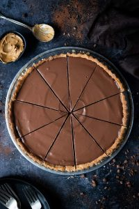 Vegan peanut butter chocolate tart cut into slices on a dark background with chocolate curls, plates, forks, a bowl of peanut butter and a brown cloth.