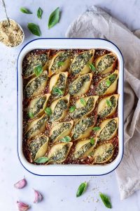 Vegan spinach and ricotta stuffed pasta shells in a white enamel dish on a marble background with fresh basil, vegan parmesan and a cream cloth.