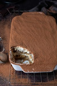 A white dish of vegan tiramisu with a spoonful removed on a wire rack on a dark background dusted with cocoa powder.