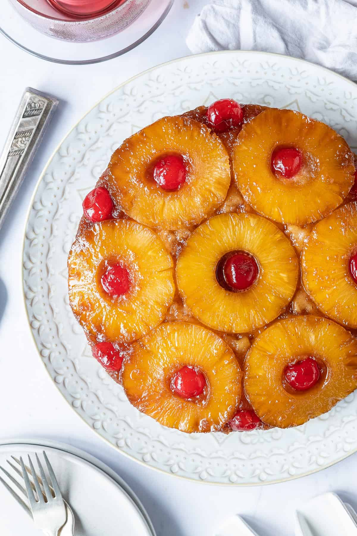 Close up of pineapple upside-down cake on a white plate.