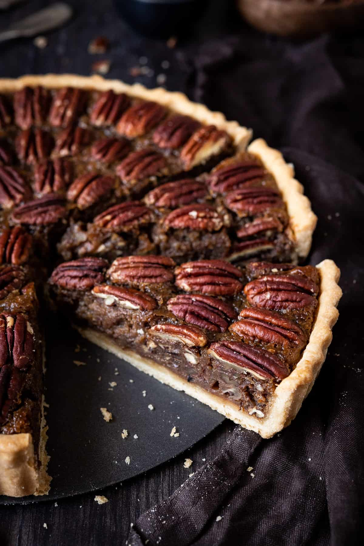 Pecan pie cut into slices on a wooden background with a brown cloth.