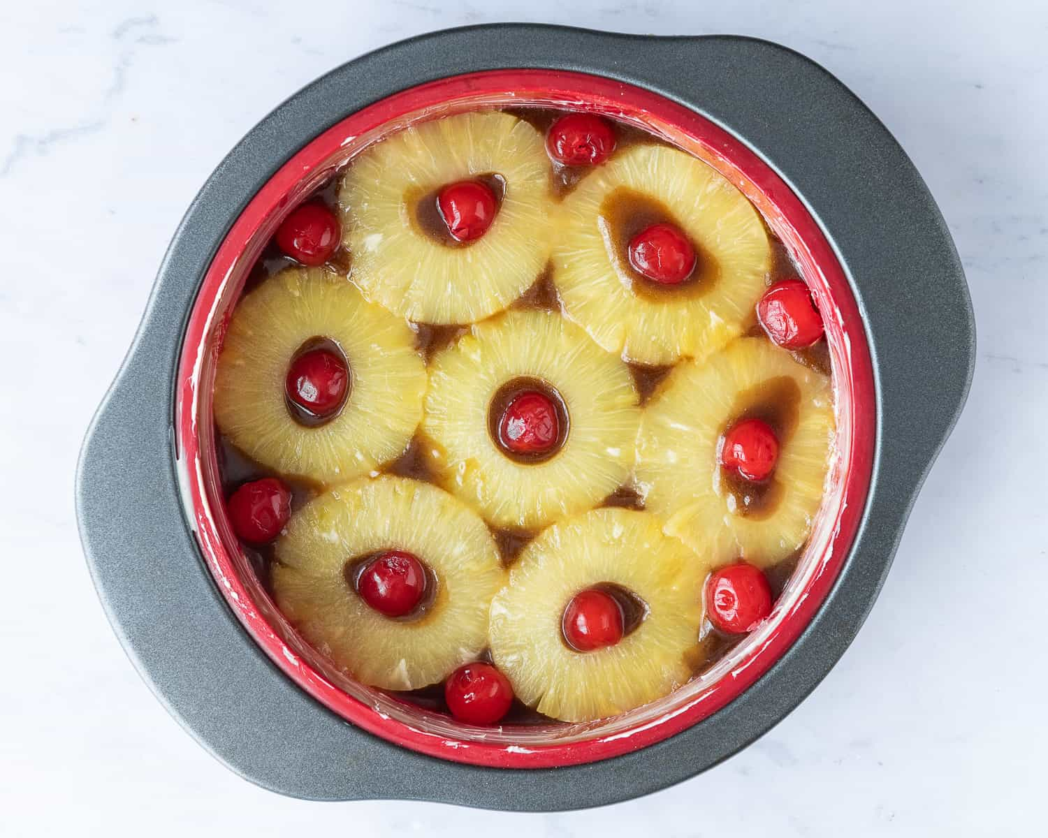 Step 1 - arranging the pineapple and cherries in the base of the cake tin.