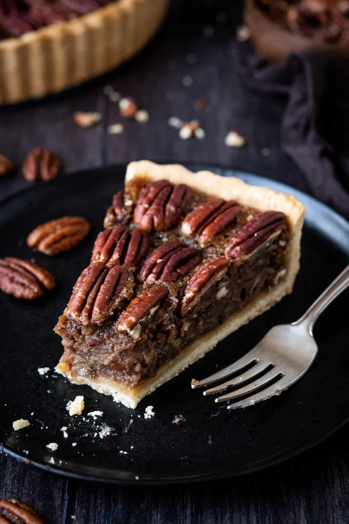 Close up of a slice of vegan pecan pie on a black plate with a forkful removed.