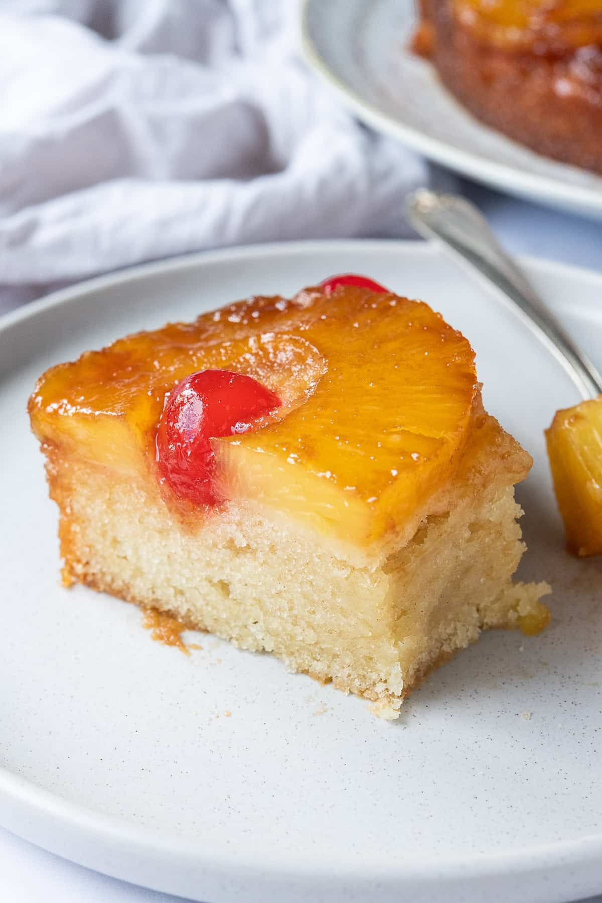 A slice of vegan pineapple upside-down cake with a forkful removed.