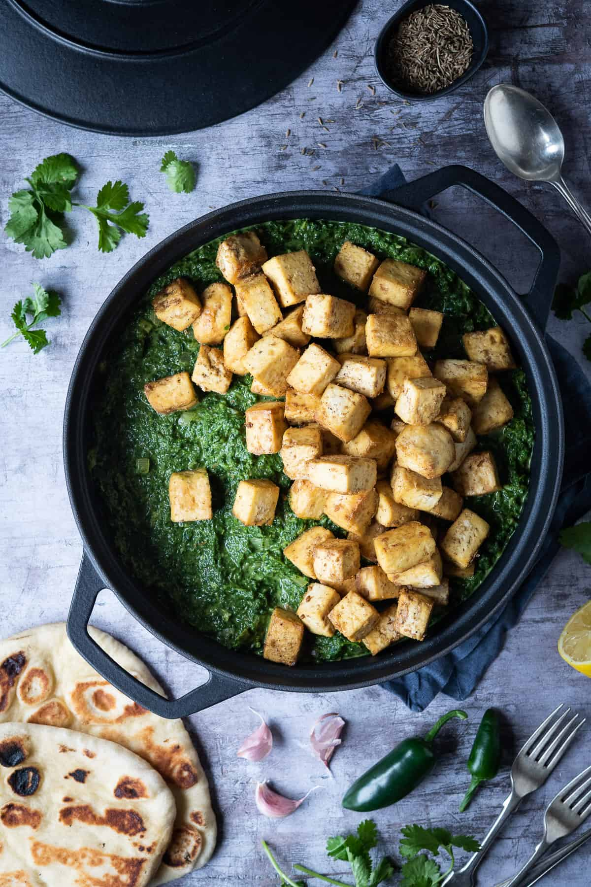 Cubes of tofu 'paneer' on top of spinach sauce in a black saucepan.