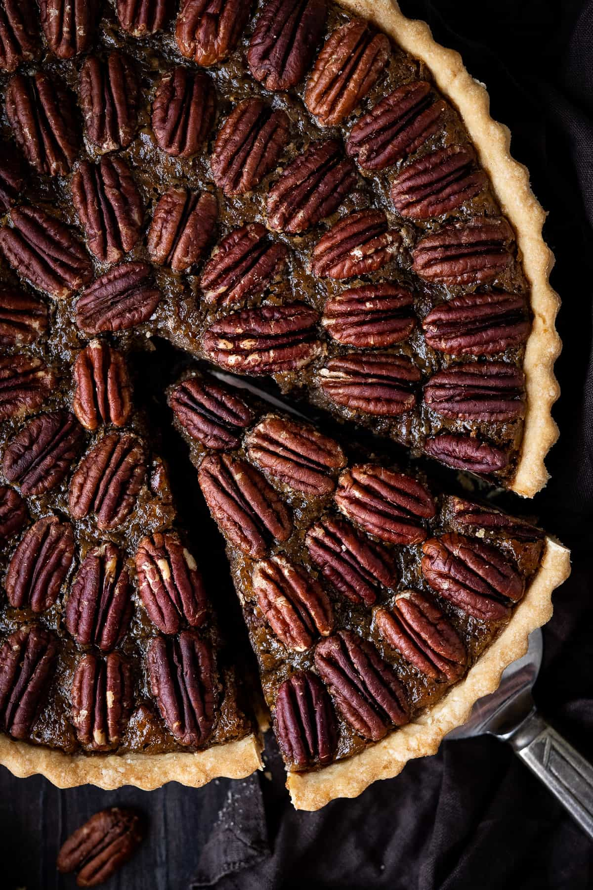 Close up of vegan pecan pie with a slice cut out.