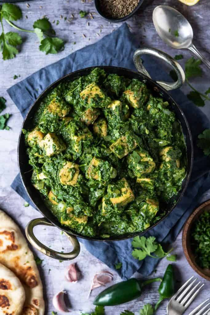 Vegan palak paneer in a kadhai pan on a grey surface surrounded by naan breads, coriander, green chillies and garlic cloves.