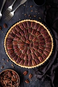 Vegan pecan pie on a wooden backdrop with a bowl of pecans, forks and a brown cloth.