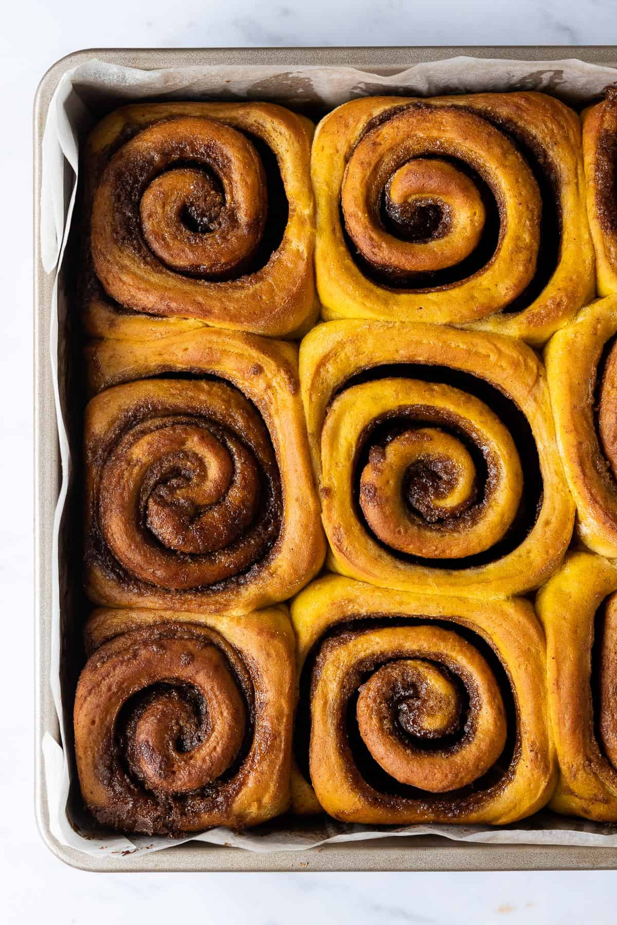 Close up of unglazed pumpkin cinnamon rolls in a metal cake tin.