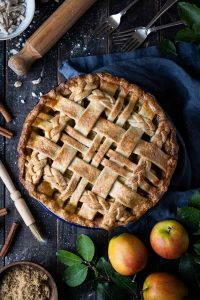 Vegan ginger apple pie on a dark wooden table surrounded by apples, a cloth, ingredients and baking equipment.