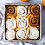 Vegan pumpkin cinnamon rolls in a metal baking tin on a grey background with mini pumpkins and a cup of coffee.