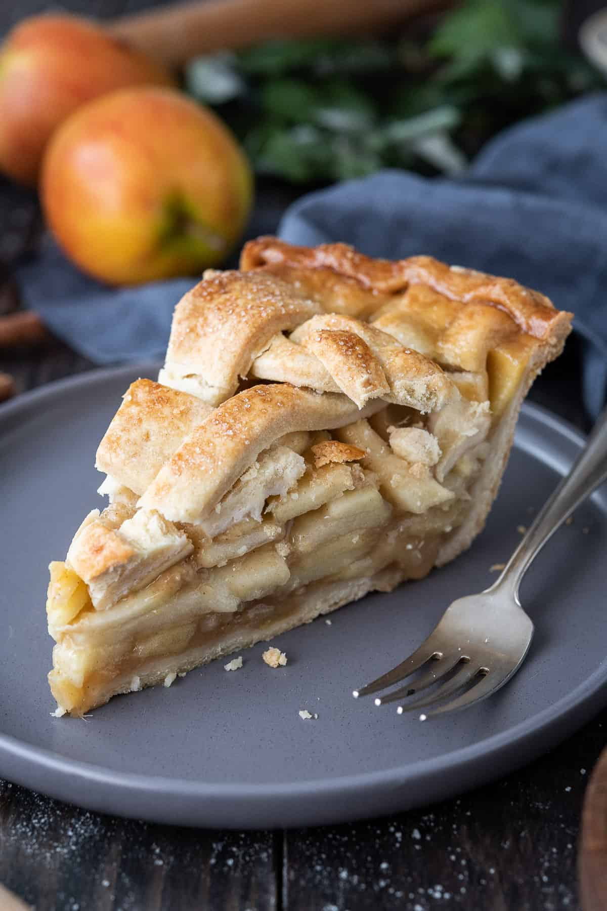 A slice of ginger apple pie on a grey plate with a fork.