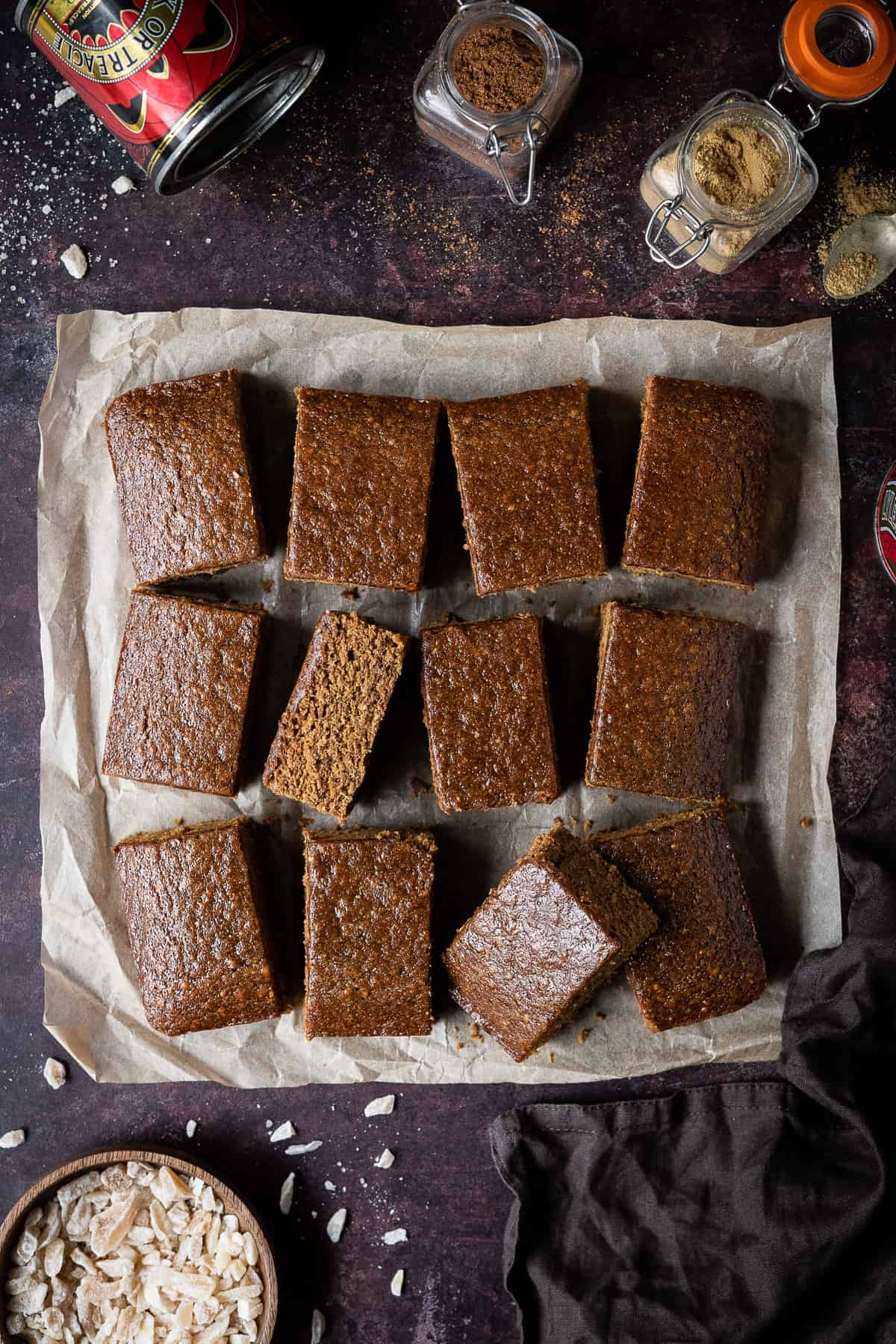 Vegan parkin on a dark brown surface with jars of spices, a tin of treacle and a bowl of crystallised ginger.